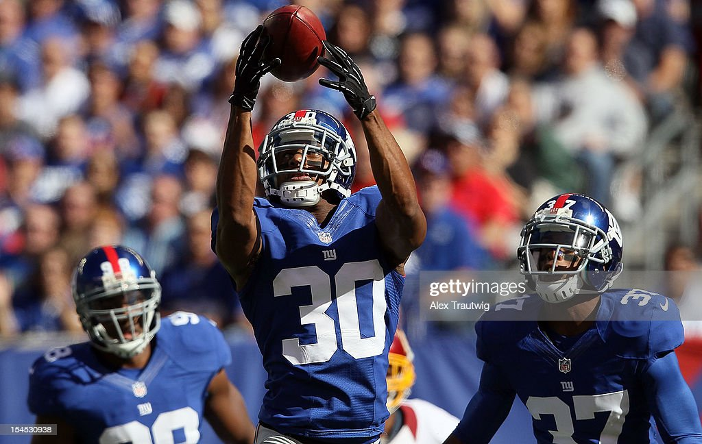 Defensive back Justin Tryon of the New York Giants downs the ball after a punt against the Washington Redskins during their game at MetLife Stadium...