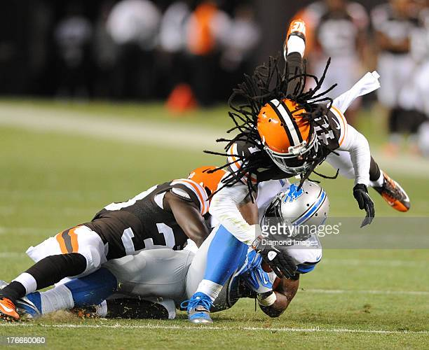 Defensive back Kent Richardson and Abdul Kanneh of the Cleveland Browns tackles running back Theo Riddick of the Detroit Lions during a game against...