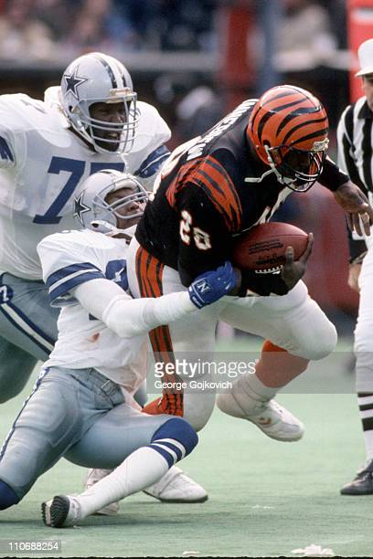 Defensive back Michael Downs of the Dallas Cowboys tackles running back Larry Kinnebrew of the Cincinnati Bengals as defensive lineman Jim Jeffcoat...