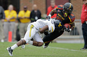 Defensive back Pat Miller of the West Virginia Mountaineers tackles running back DJ Adams of the Maryland Terrapins during the second half at Byrd...
