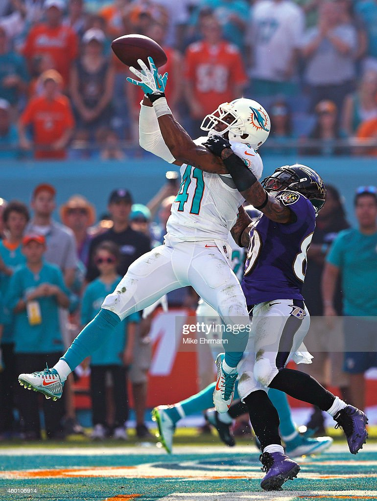 Defensive back R.J. Stanford #41 of the Miami Dolphins intercepts a second quarter pass in the endzone intended for wide receiver Steve Smith #89 of the Baltimore Ravens during a game at Sun Life Stadium on December 7, 2014 in Miami Gardens, Florida.
