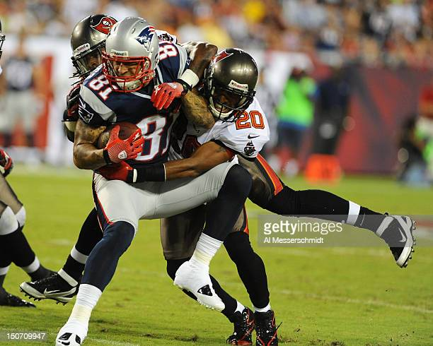 Defensive back Ronde Barber of the Tampa Bay Buccaneers tackles tight end Aaron Hernendez of the New England Patriots at Raymond James Stadium in a...