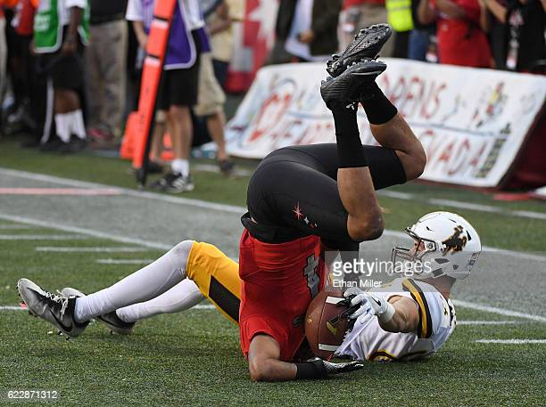 Defensive back Torry McTyer of the UNLV Rebels intercepts the ball in the third overtime against wide receiver Jake Maulhardt of the Wyoming Cowboys...