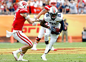 Defensive back Trovon Reed of the Auburn Tigers intercepts a pass intended for wide receiver Jordan Fredrick of the Wisconsin Badgers during the...
