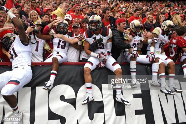 Defensive back Zach Dancel of the Maryland Terrapins and teammates jump into the crowd before playing the West Virginia Mountaineers during an NCAA...