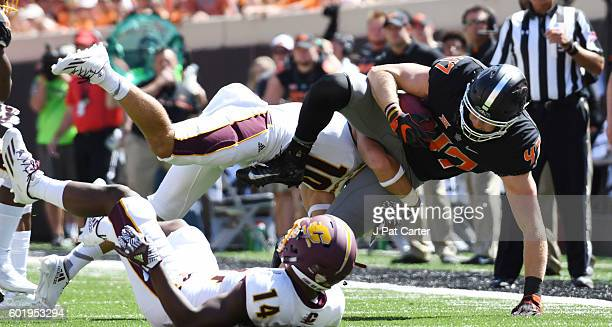 Defensive back Zach Oakley of the Central Michigan Chippewas stops tight end Blake Jarwin of the Oklahoma State Cowboys during the first half of a...