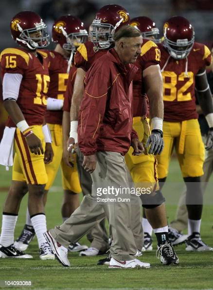 Defensive coordinator Monte Kiffin watches the USC Trojans warm up for their game with the Virginia Cavaliers at Los Angeles Memorial Coliseum on...