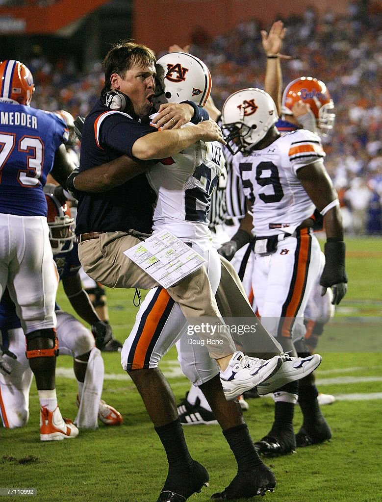 Defensive coordinator Will Muschamp of the Auburn Tigers jumps into the arms of defensive back Patrick Lee after Lee helped cause a fumble late in...