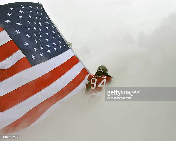 Defensive end Adrian Clayborn of the Tampa Bay Buccaneers runs onto the field carrying the American flag before play against the San Francisco 49ers...