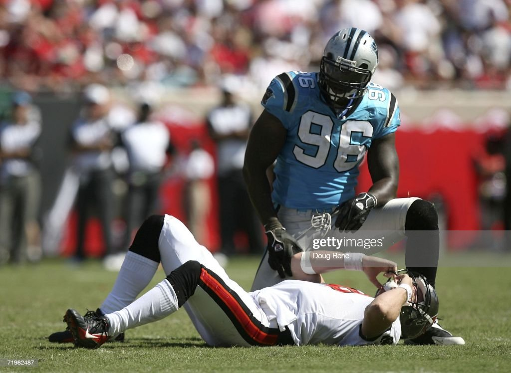 Defensive end Al Wallace #96 of the Carolina Panthers kneels over quarterback Chris Simms #2 of the Tampa Bay Buccaneers after Simms was hit by Wallace in the fourth quarter on September 24, 2006 at Raymond James Stadium in Tampa, Florida. The Panthers defeated the Buccaneers 26-24.