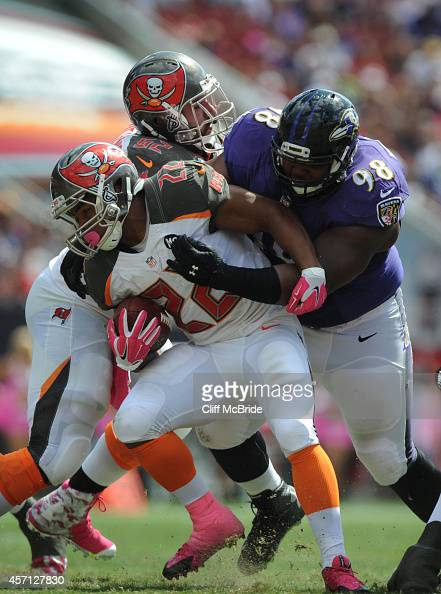 Defensive end Brandon Williams of the Baltimore Ravens tackles running back Doug Martin of the Tampa Bay Buccaneers at Raymond James Stadium on...