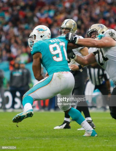 Defensive end Cameron Wake of Miami Dolphins is held by offensive lineman Ryan Ramczyk of New Orleans Saints during the New Orleans Saints...
