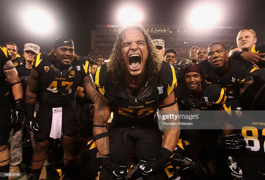 Defensive end Carl Bradford #52 of the Arizona State Sun Devils celebrates alongside teammates after defeating the Wisconsin Badgers 32-30 in the college football game at Sun Devil Stadium on September 14, 2013 in Tempe, Arizona.