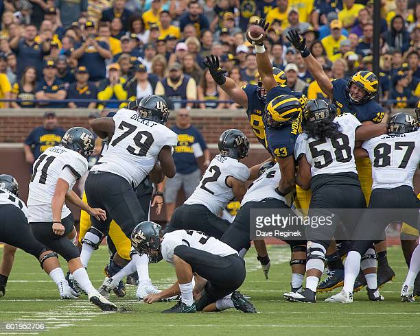 Defensive end Chris Wormley of the Michigan Wolverines blocks a field goal attempt by Mathew Wright of the UCF Knights during a college football game...