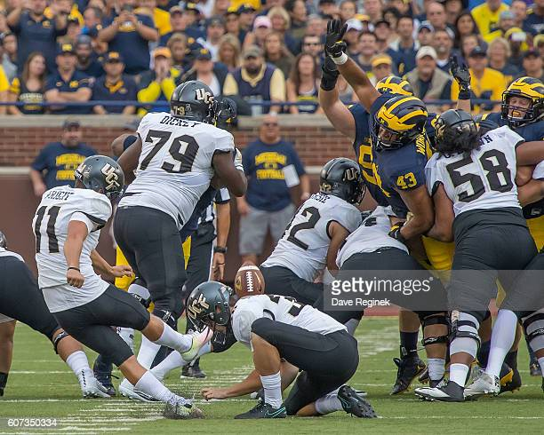 Defensive end Chris Wormley of the Michigan Wolverines reaches to try and block a field goal attempt by Mathew Wright of the UCF Knights during a...
