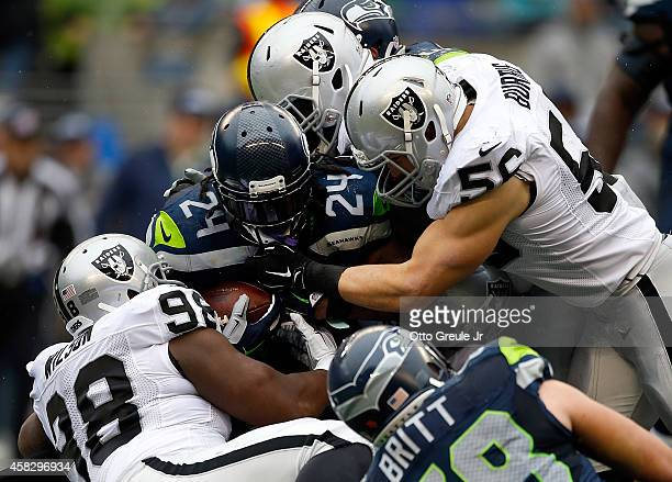 Defensive end CJ Wilson and middle linebacker Miles Burris of the Oakland Raiders gang up to tackle running back Marshawn Lynch of the Seattle...