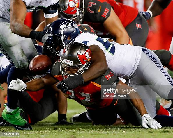 Defensive End Cliff Avril of the Seattle Seahawks strips the ball loose from Running back Doug Martin of the Tampa Bay Buccaneers during the game at...