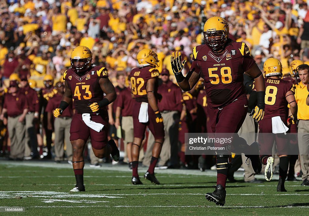defensive end Davon Coleman #43 and linebacker Salamo Fiso #58 of the Arizona State Sun Devils run onto the field during the college football game against the Washington Huskies at Sun Devil Stadium on October 19, 2013 in Tempe, Arizona. The Sun Devils defeated the Huskies 53-24.