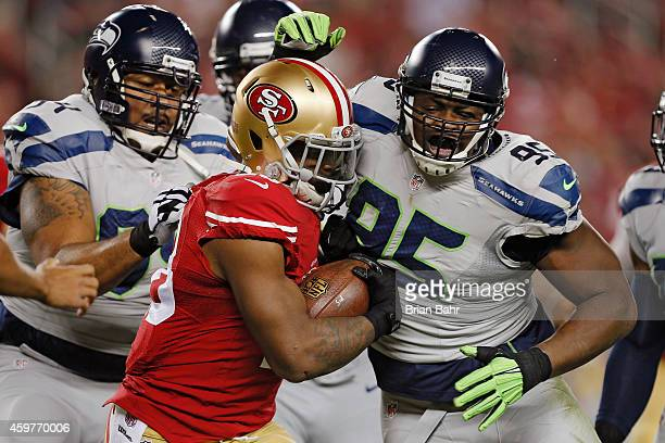Defensive end Demarcus Dobbs of the Seattle Seahawks wraps up running back Carlos Hyde of the San Francisco 49ers for a loss of a yard in the first...