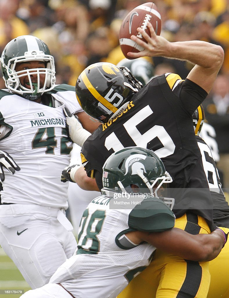 Defensive end Denzel Drone #42 and linebacker Denicos Allen #28 of the Michigan State Spartans put pressure on quarterback Jake Rudock #15 of the Iowa Hawkeyes during the fourth quarter past defensive end Brandon Harold #91 on October 5, 2013 at Kinnick Stadium in Iowa City, Iowa. Michigan State won 26-14.