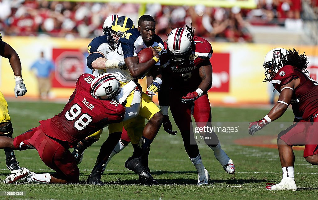 Defensive end <a gi-track='captionPersonalityLinkClicked' href=/galleries/search?phrase=Jadeveon+Clowney&family=editorial&specificpeople=7471550 ng-click='$event.stopPropagation()'>Jadeveon Clowney</a> #7 of the South Carolina Gamecocks tackles quarterback Devin Gardner #12 of the Michigan Wolverines during the Outback Bowl Game at Raymond James Stadium on January 1, 2013 in Tampa, Florida.