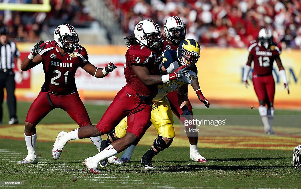 Defensive end <a gi-track='captionPersonalityLinkClicked' href=/galleries/search?phrase=Jadeveon+Clowney&family=editorial&specificpeople=7471550 ng-click='$event.stopPropagation()'>Jadeveon Clowney</a> #7 of the South Carolina Gamecocks rushes the quarterback of the Michigan Wolverines during the Outback Bowl Game at Raymond James Stadium on January 1, 2013 in Tampa, Florida.