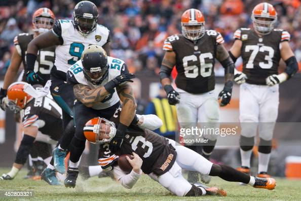 Defensive end Jason Babin of the Jacksonville Jaguars tackles quarterback Brandon Weeden of the Cleveland Browns during the second half at...