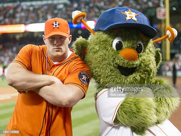 Defensive end JJ Watt of the Houston Texans poses with Houston Astros mascot Orbit after throwing out the first pitch during opening night at Minute...