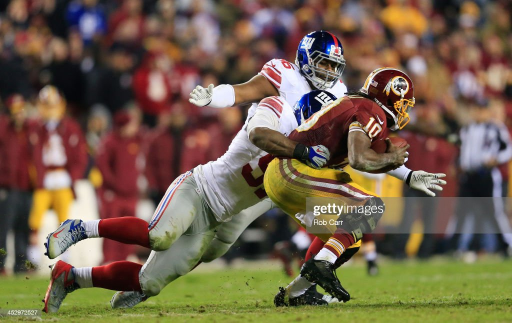 Defensive end Justin Tuck and defensive tackle Johnathan Hankins of the New York Giants sack quarterback Robert Griffin III of the Washington...