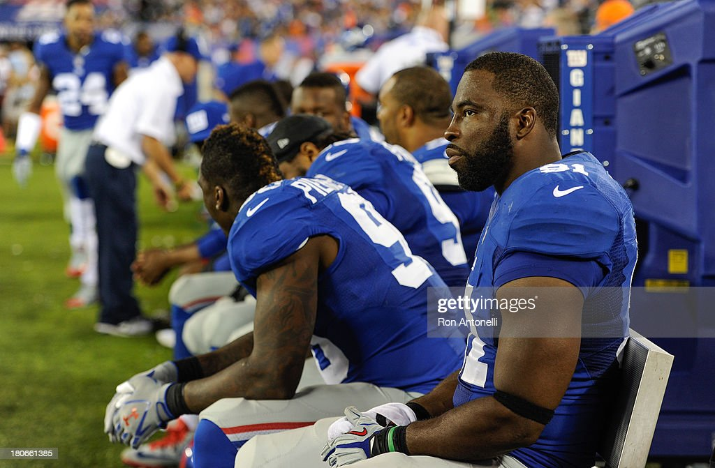Defensive end <a gi-track='captionPersonalityLinkClicked' href=/galleries/search?phrase=Justin+Tuck&family=editorial&specificpeople=748769 ng-click='$event.stopPropagation()'>Justin Tuck</a> #91 of the New York Giants on the bench during the 2nd half of the Denver Broncos 41-23 win over the New York Giants at MetLife Stadium on September 15, 2013 in East Rutherford, New Jersey.