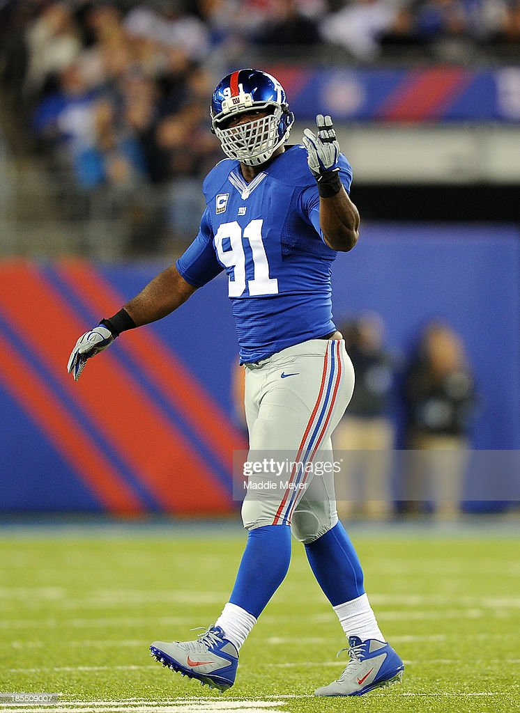 Defensive end Justin Tuck #91 of the New York Giants reacts after a defensive play against the Minnesota Vikings during a game at MetLife Stadium on October 21, 2013 in East Rutherford, New Jersey.