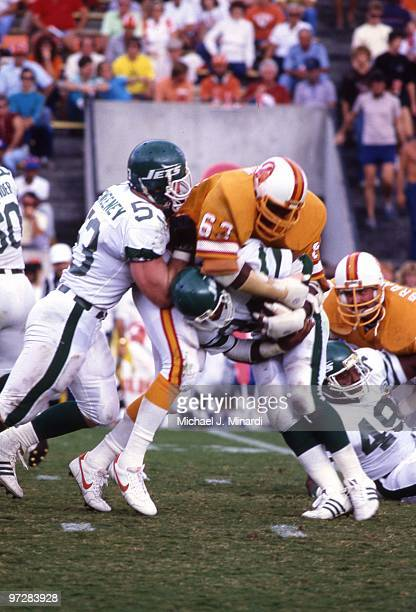 Defensive end Lee Roy Selmon of the Tampa Bay Buccaneers makes a tackle on a New York Jets ball carrier while being blocked by center Jim Sweeney of...
