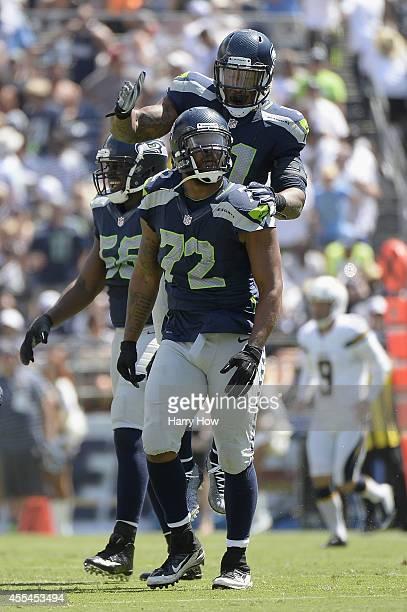 Defensive end Michael Bennett of the Seattle Seahawks and outside linebacker Bruce Irvin of the Seattle Seahawks celebrate a defensive stop against...