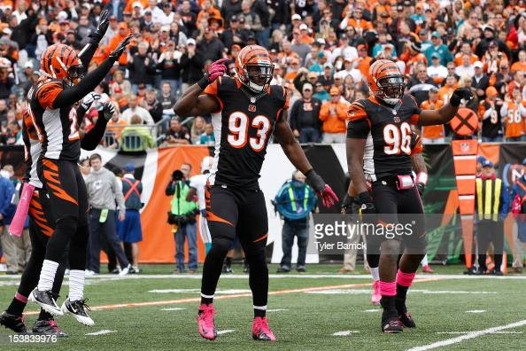 Defensive end Michael Johnson #93 of the Cincinnati Bengals celebrates with teammates Carlos Dunlap and Terence Newman after stopping a Miami...