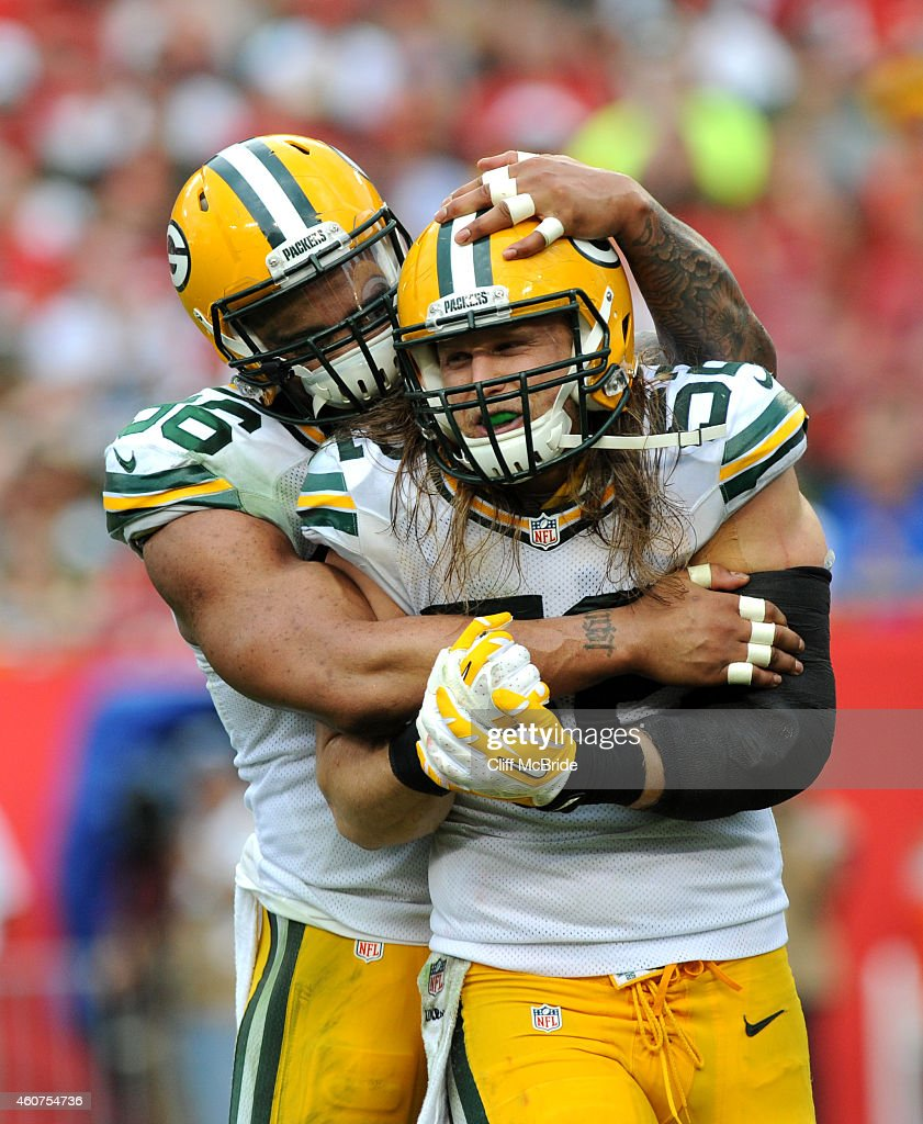Defensive end Mike Neal of the Green Bay Packers celebrates a sack by teammate outside linebacker Clay Matthews of the Green Bay Packers against the...