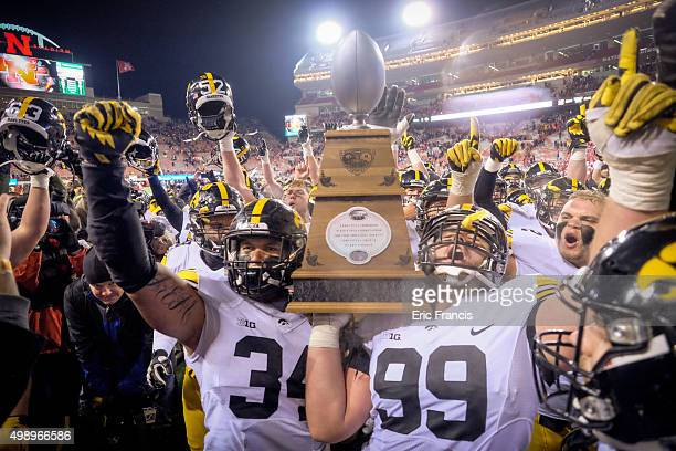 Defensive end Nate Meier and defensive lineman Nathan Bazata and the Iowa Hawkeyes celebrate with The Heros Game Trophy after their game against the...