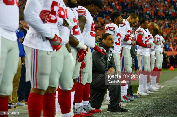 Defensive end Olivier Vernon of the New York Giants who did not suit up for the game against the Denver Broncos kneeled on the sideline while...