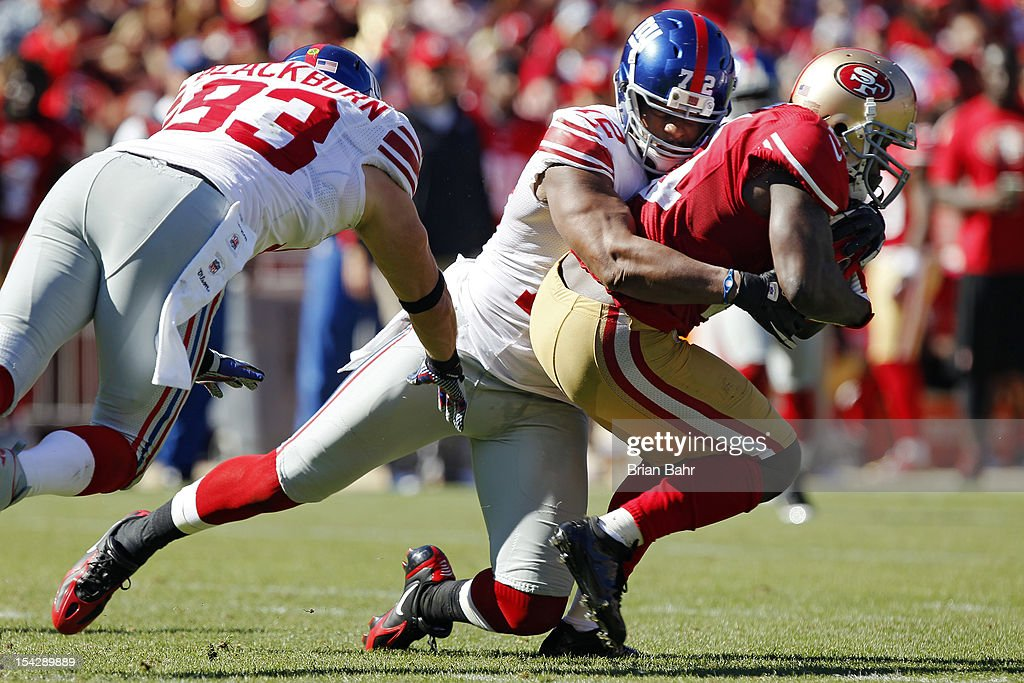 Defensive end Osi Umenyiora of the New York Giants tackles running back Frank Gore of the San Francisco 49ers in the second quarter in the second...