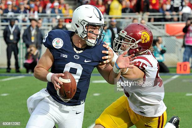 Defensive end Porter Gustin of the USC Trojans attempts to tackle quarterback Trace McSorley of the Penn State Nittany Lions in the first half of the...