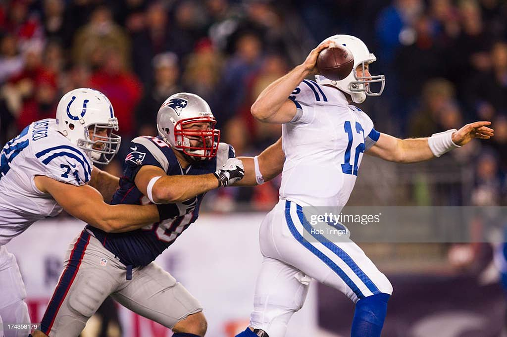 Defensive end Rob Ninkovich of the New England Patriots is stopped from sacking quarterback Andrew Luck of the Indianapolis Colts by tackle Anthony...