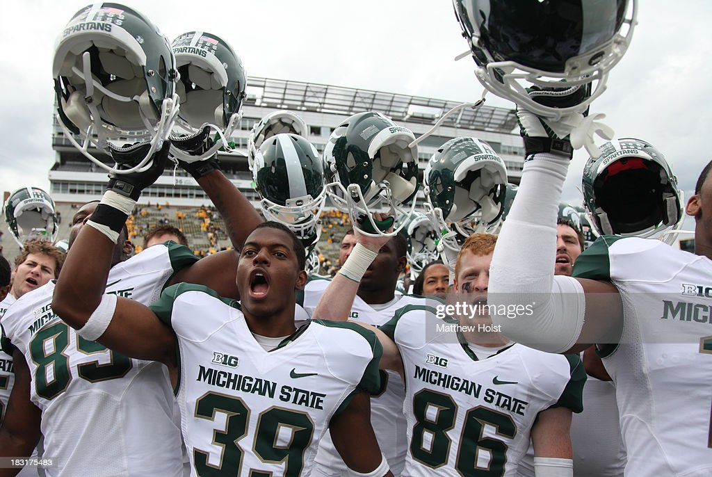 Defensive end Shilique Calhoun #89, Jermaine Edmondson #39 and Matt Macksood #86 of the Michigan State Spartans sing their fight song after their match-up against the Iowa Hawkeyes on October 5, 2013 at Kinnick Stadium in Iowa City, Iowa. Michigan State won 26-14.