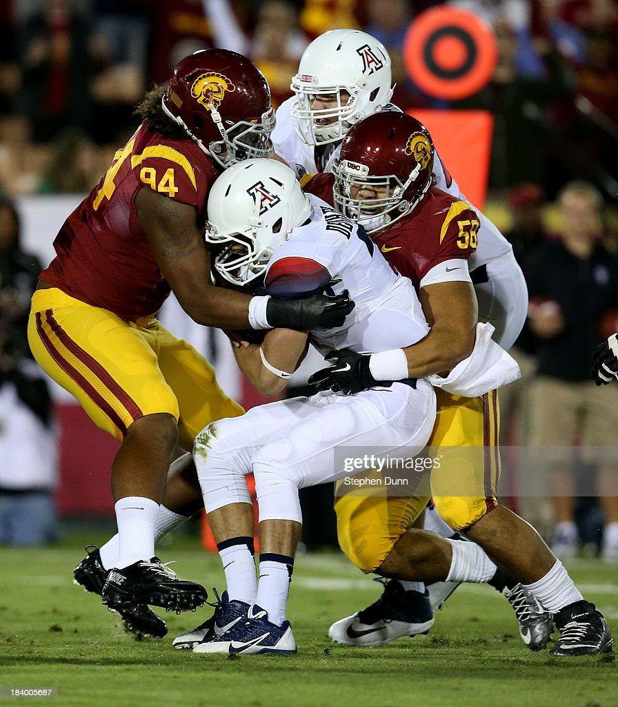 Defensive ends Leonard Williams #94 and J.R. Tavai #58 of the USC Trojans tackle quarterback B.J. Denker #7 of the Arizona Wildcats at Los Angeles Coliseum on October 10, 2013 in Los Angeles, California.