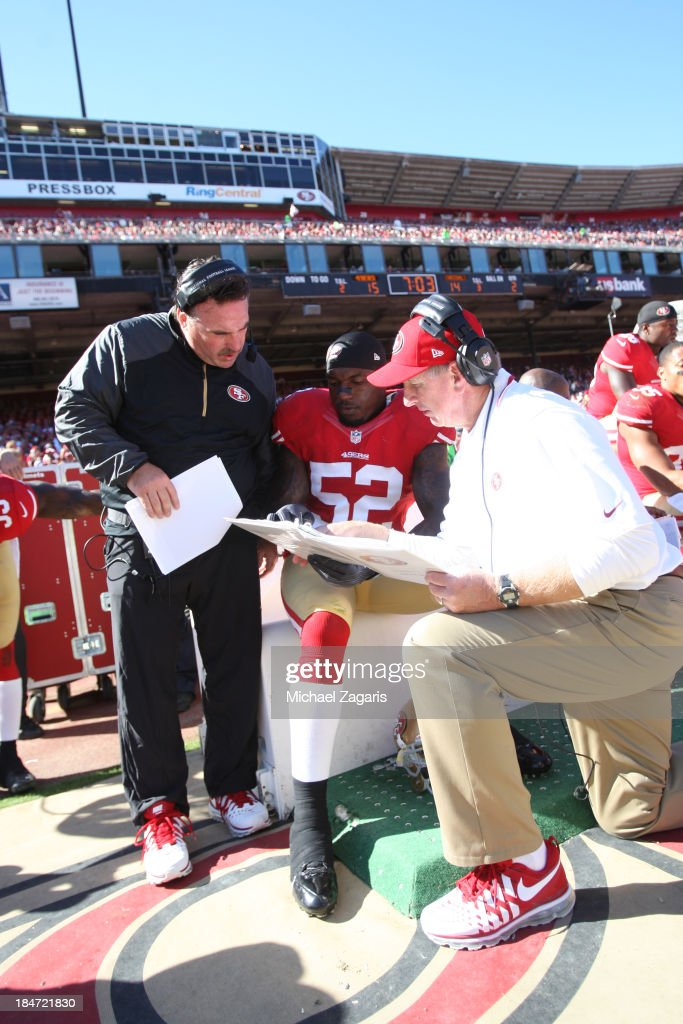 Defensive Line Coach Jim Tomsula and Linebackers Coach Jim Leavitt of the San Francisco 49ers talk with Patrick Willis during the game against the...