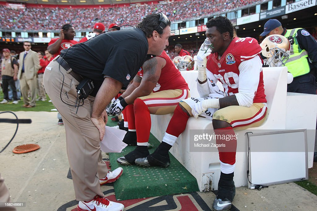 Defensive Line Coach Jim Tomsula of the San Francisco 49ers talks with Aldon Smith #99 during the game against the Miami Dolphins at Candlestick Park on December 9, 2012 in San Francisco, California. The 49ers defeated the Dolphins 27-13.