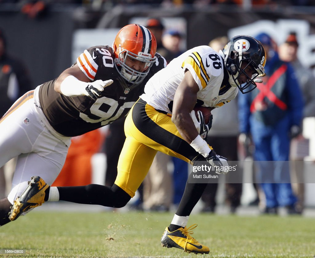 Defensive lineman Billy Winn #90 of the Cleveland Browns tackles wide receiver Emmanuel Sanders #88 of the Pittsburgh Steelers at Cleveland Browns Stadium on November 25, 2012 in Cleveland, Ohio.
