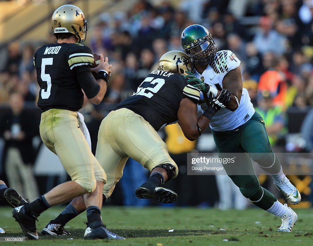 Defensive lineman DeForest Buckner #44 of the Oregon Ducks rushes against the block of offensive linesman Daniel Munyer #52 of the Colorado Buffaloes toward quarterback Connor Wood #5 of the Colorado Buffaloes at Folsom Field on October 5, 2013 in Boulder, Colorado. The Ducks defeated the Buffs 57-16.