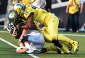 Defensive lineman DeForest Buckner of the Oregon Ducks sacks Quarterback Connor Cook of the Michigan State Spartans during the third quarter of the...