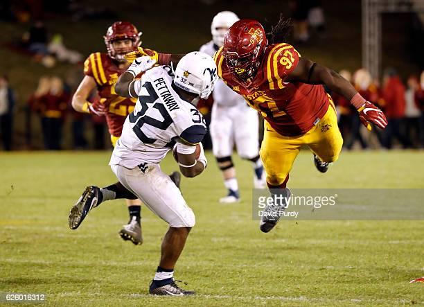 Defensive lineman Demond Tucker of the Iowa State Cyclones tackles running back Martell Pettaway of the West Virginia Mountaineers as he rushed for...