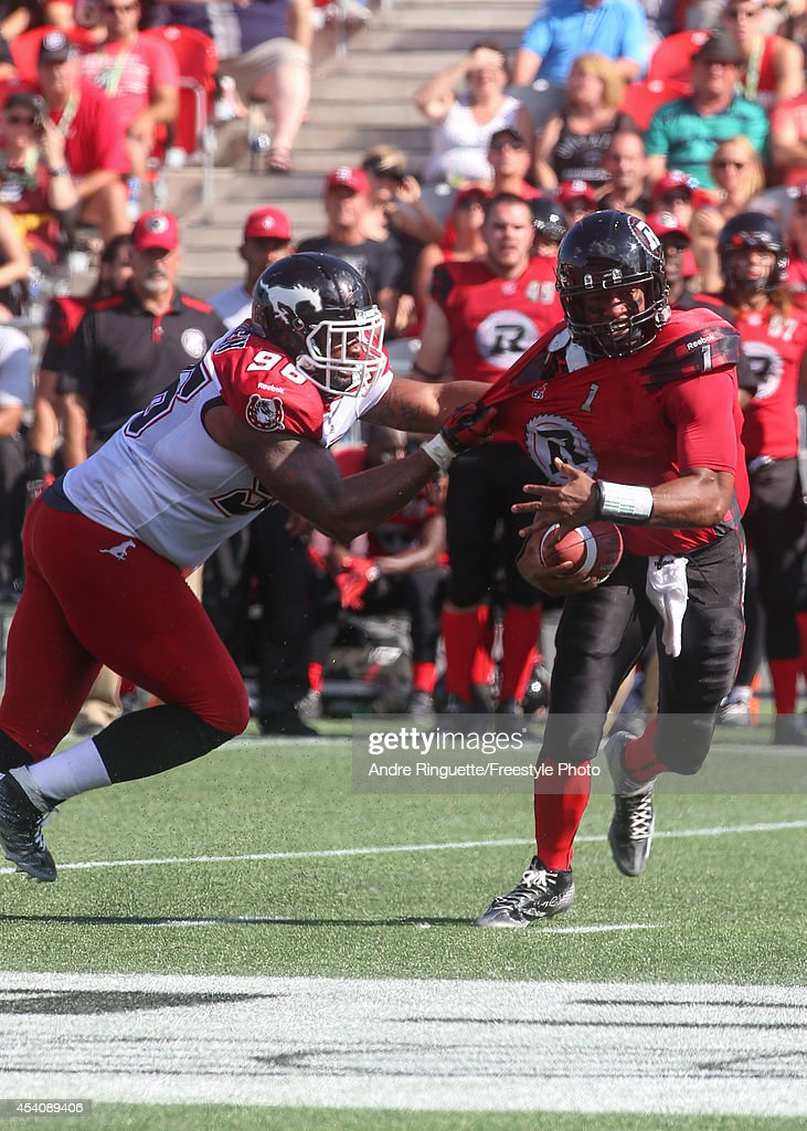 Defensive lineman Demonte' Bolden #96 of the Calgary Stampeders grabs a hold of Henry Burris #1 of the Ottawa Redblacks during a CFL game at TD Place Stadium on August 24, 2014 in Ottawa, Ontario, Canada.