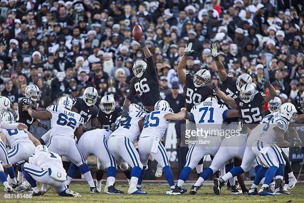 Defensive lineman Denico Autry and defensive tackle Dan Williams of the Oakland Raiders try to block a point after touchdown against kicker Adam...